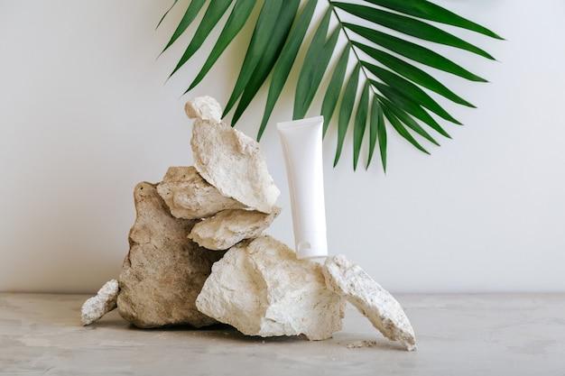 Natürliches schönheitskosmetikschlauchmodell für die hautpflege mit palmblattpflanze auf grauem hintergrund des steinsockels. natürlicher steinhaufen aus balanciersteinen mit kosmetischer tube zur körperpflegecreme.
