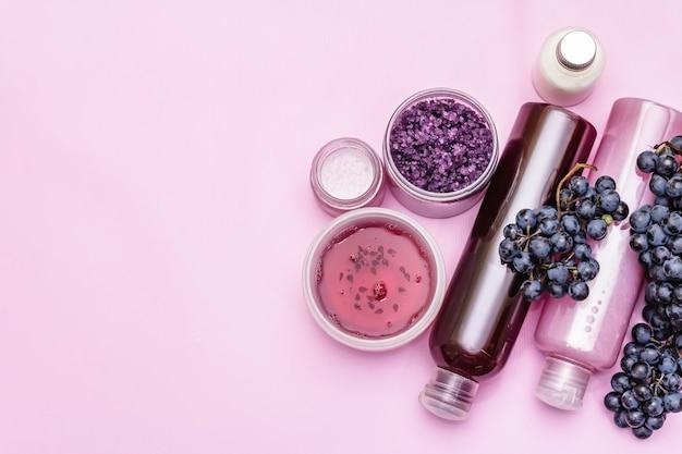 Natürliches spa-zubehör mit reifen trauben. frische zutaten für eine gesunde und schöne selbstpflege. rosa hintergrund, draufsicht