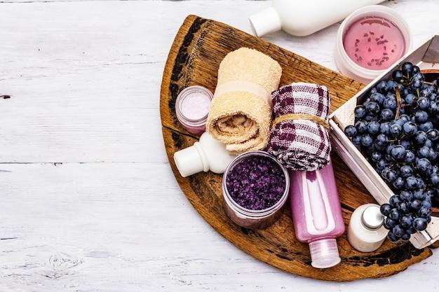 Natürliches spa-zubehör mit reifen trauben. frische zutaten für eine gesunde und schöne selbstpflege. weißer holzbretterhintergrund, draufsicht