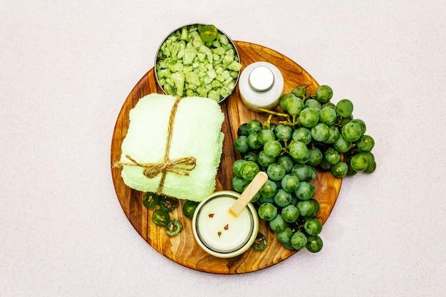 Natürliches spa-zubehör und grüne trauben auf einem holzteller, draufsicht