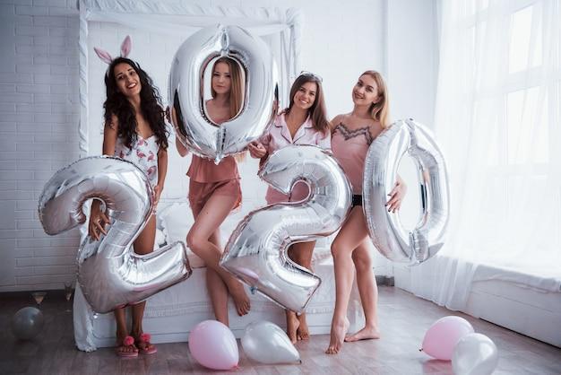 Natürliches tageslicht durch das fenster. vier mädchen in rosa und weißen kleidern stehen mit silberfarbenen luftballons. vorstellung von einem guten neuen jahr