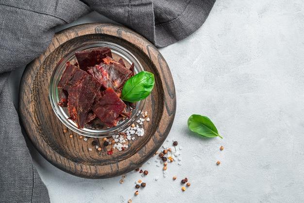 Natürliches trockenfleisch in kleine stücke geschnitten mit basilikum und gewürzen an einer grauen wand. draufsicht mit kopienraum.