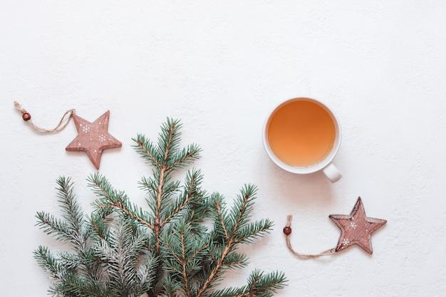 Natürliches weihnachtsdekor aus tannenzweigen und einer tasse grünem tee auf weißem hintergrund.