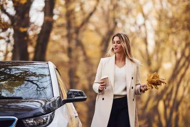 Natur genießen. mädchen haben eine herbstreise mit dem auto. modernes brandneues auto im wald.