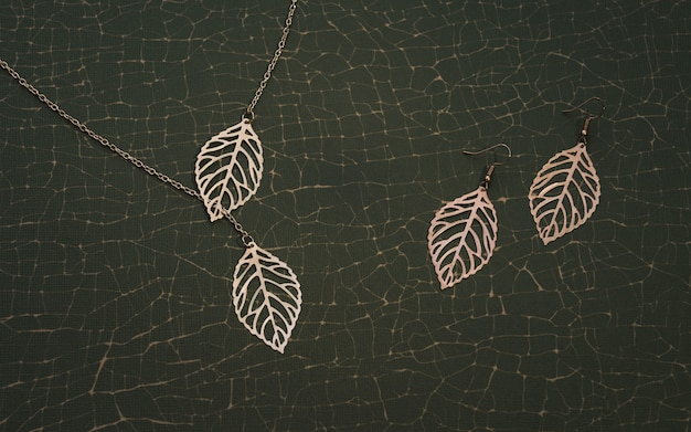 Natur inspiriertes goldenes accessoires-set. mädchenhalskette und ohrringe paar auf rissigem grünem hintergrund.