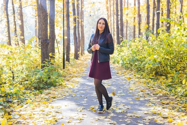 Natur-, jahreszeit- und personenkonzept - modefrau, die im herbstpark geht