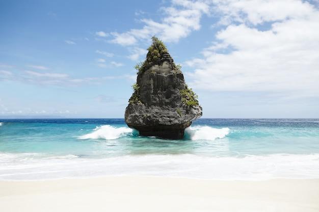 Natur, tourismus, reisen, abenteuer, paradies und seelandschaft. szenische ansicht der isolierten felseninsel mit grünen tropischen bäumen in der mitte des ozeans. schöner und friedlicher abgelegener ort, ideal für reisende
