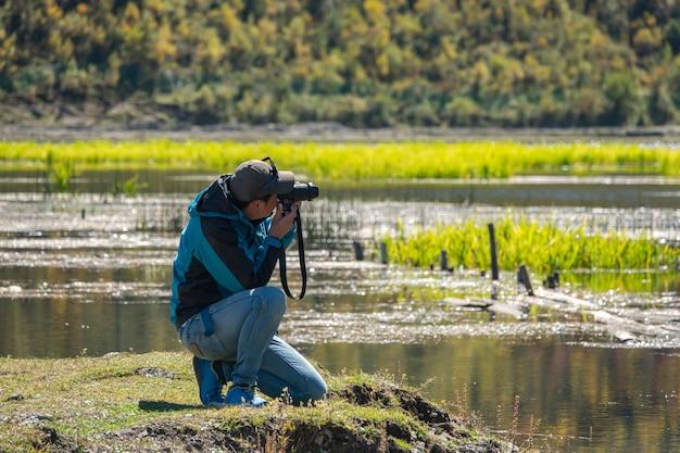 Naturfotograf, der im freien schießt, reist und die berühmten attraktionen im chenghai see, china besucht.