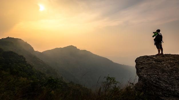 Naturfotograf im berg. sonnenlicht und himmel in bergen.