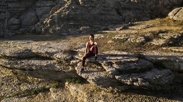 Naturherz mit der jungen frau, die yoga tut