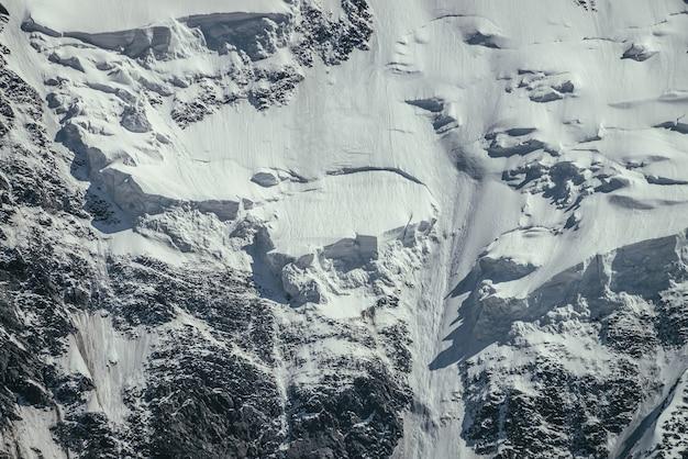 Naturhintergrund der großen felsigen schneebedeckten bergwand mit weißem gletscher und schneegesims hautnah. schöne natürliche textur des sonnenbeschienenen schneebedeckten berghangs. voller rahmen von schwarz-weißen hochgebirgen.
