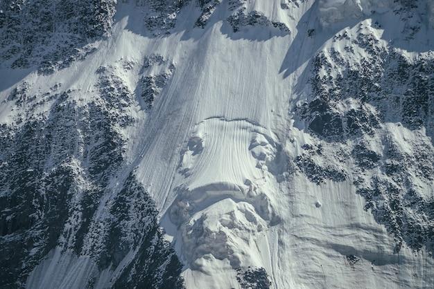 Naturhintergrund der großen felsigen schneebedeckten bergwand mit weißem gletscher und schneegesims hautnah.