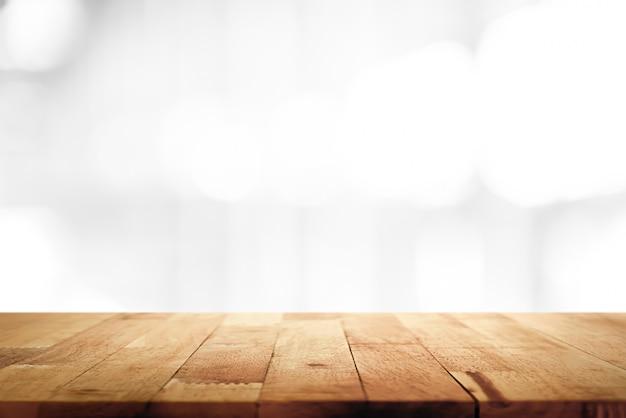Naturholz-tischplatte auf unscharfem weißem hintergrund