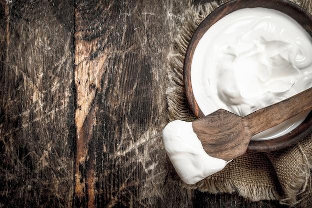 Naturjoghurt in einer schüssel. auf einem hölzernen hintergrund.