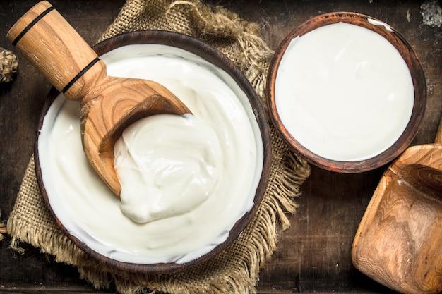 Naturjoghurt in einer schüssel. auf einem rustikalen hintergrund.