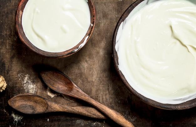 Naturjoghurt in einer schüssel mit einem löffel auf einem holztisch
