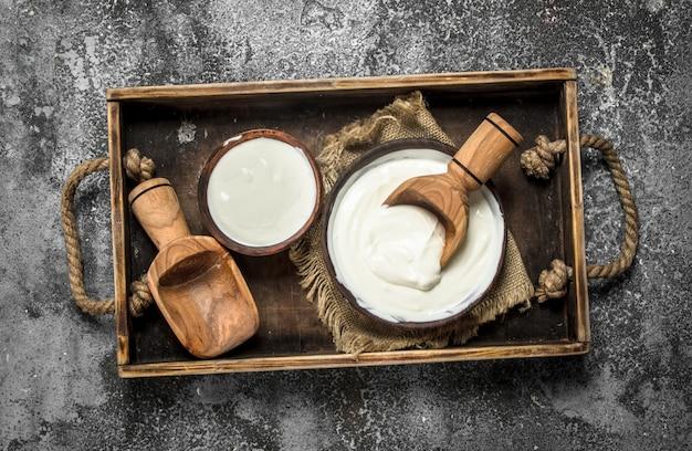 Naturjoghurt mit einer kugel in einer schüssel. auf einem rustikalen hintergrund