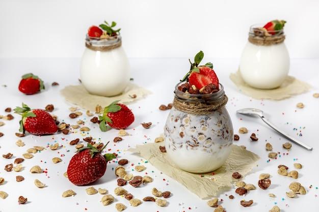 Naturjoghurt mit müsli und erdbeeren im glas. weißer hintergrund.