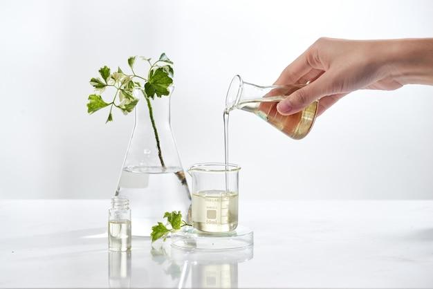 Naturkosmetik-hautpflege-serumverpackung mit blatt, hausgemachtem öl und schönheitsvitaminbestandteil. bio-produktforschung der leere flaschenbehälter, biowissenschaft. alternative medizin. spa.