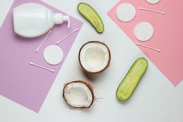 Naturkosmetik, hautpflegeprodukte. kokosnuss, gurken, flasche sahne, kosmetisches zubehör auf farbigem hintergrund. minimalistisches schönheitskonzept.