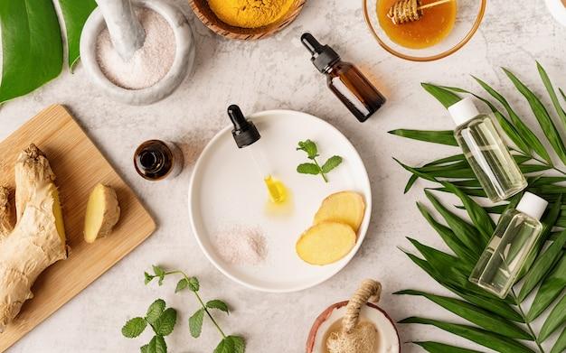 Naturkosmetik-inhaltsstoffe für haut-, körper- und haarpflege. draufsichtflaschen mit gesichtsbehandlungsprodukt, tropische blätter