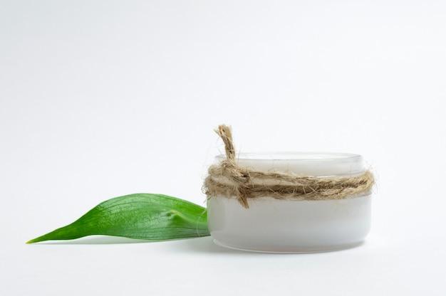 Naturkosmetik-konzept. kosmetisches glas mit gesichtscreme und grünem blatt. weißer hintergrund.