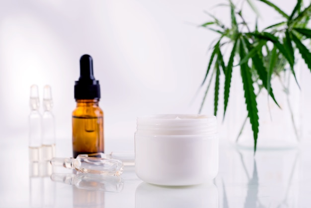 Naturkosmetik mit cannabisöl. weißes, sauberes glas mit kosmetikcreme und frischen grünen hanfblättern.
