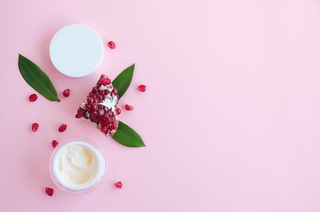 Naturkosmetik mit fruchtsäuren, mit granatapfelextrakt auf rosa hintergrund. logo, flat lay, vorlage, banner, leerzeichen, kopierraum. schönheitskonzept