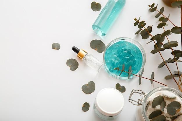 Naturkosmetik-serum-creme-gel mit eukalyptusblättern. hautpflege kosmetik spa kräuterbehandlung und aromatherapie auf weißem hintergrund mit kopienraum.