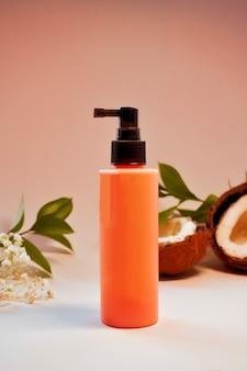 Naturkosmetikflasche für creme, gel, lotion. kosmetikproduktverpackung, leere rosa plastikbehälterschablone an der wand der natürlichen kokosnuss und der blätter.