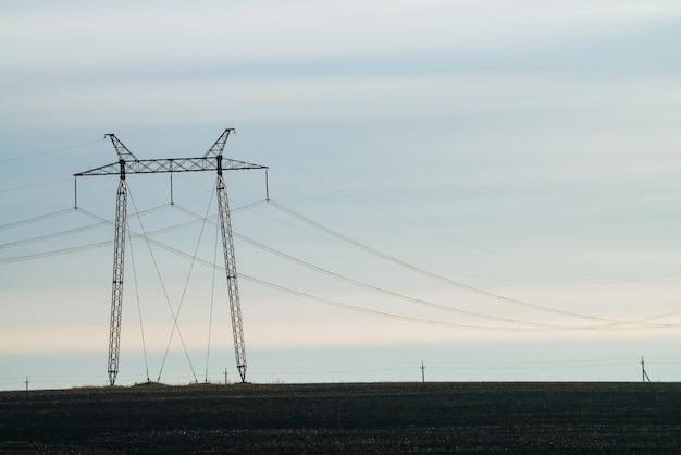 Naturlandschaft mit silhouetten von stromleitungen im feld
