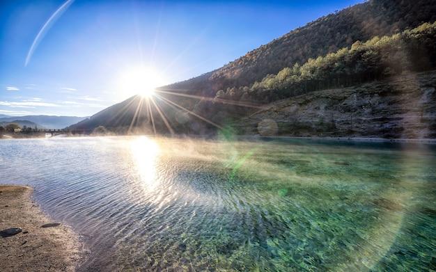 Naturlandschaft und strahl des sonnenlichts über white water river.