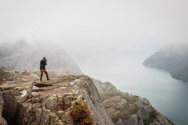 Naturphotographtourist mit kameraaufnahmen bei der stellung auf dem berg.