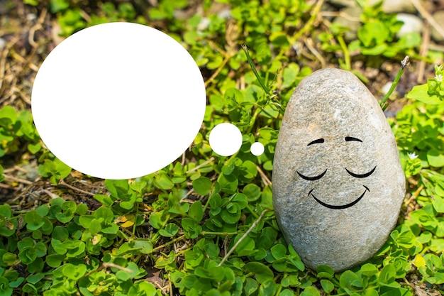 Naturstein mit gezeichnetem lustigem gesicht und sprechblase mit kopienraum. leere vorlage für werbung, verkaufsbanner, motivationsplakat usw.
