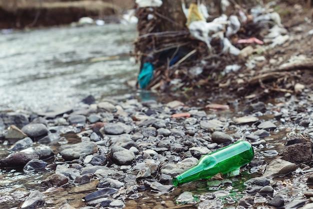 Naturteich mit plastikflaschen, die von menschen hinterlassen wurden. ökologische katastrophe der wasserressourcen.
