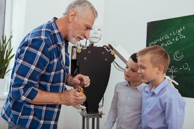 Naturwissenschafts-lehrer. freudiger alter mann, der mit seinen schülern spricht, während er ihnen von wissenschaft erzählt