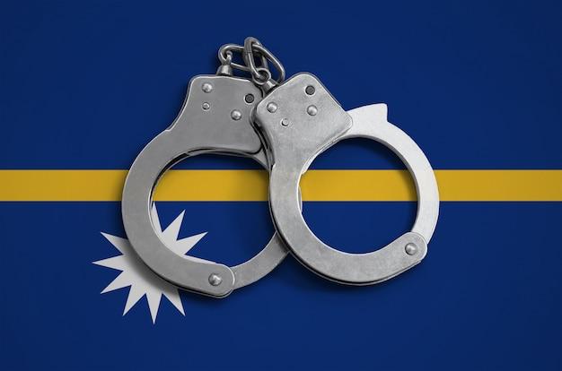 Nauru flagge und polizeihandschellen. das konzept der einhaltung des gesetzes im land und des verbrechensschutzes