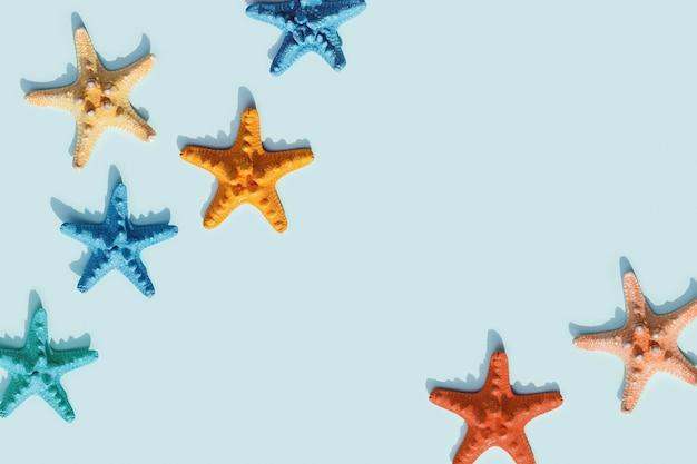 Nautische szene mit bunten seesternen auf blauem hintergrund. fröhliche, helle und sommerliche stimmung flach.