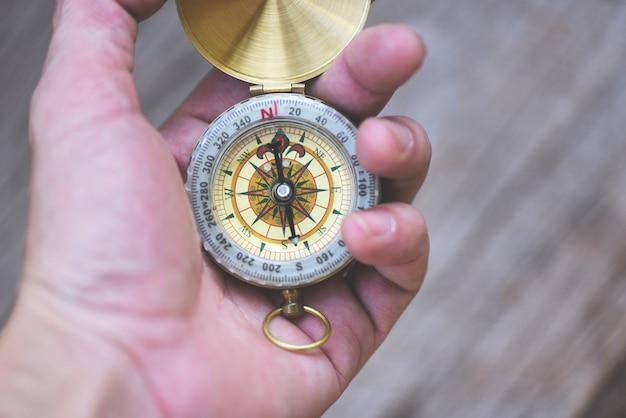 Navigationskompassreise- und touristenkonzept. mannforscher, der richtung mit kompass für karte sucht
