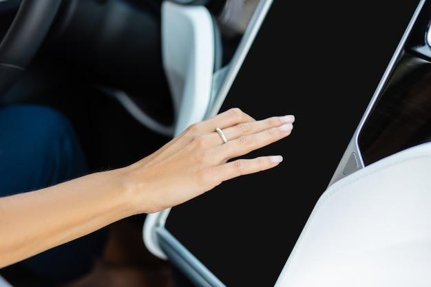 Navigationssystem. nahaufnahme einer frau, die einen schönen ring mit dem navigationssystem in ihrem auto trägt?