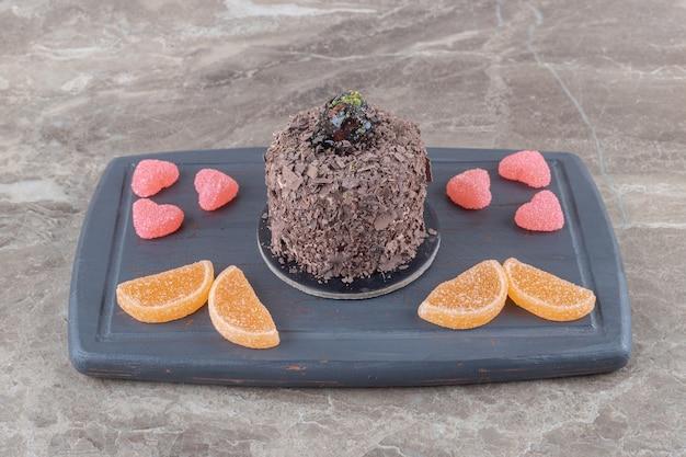 Navy board mit schokoladenkuchen und marmeladenbündeln auf marmoroberfläche