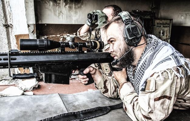 Navy seal-scharfschützenteam, bewaffnetes 50-kaliber-scharfschützengewehr, das territorium beobachtet, im hinterhalt wartet, feindliche streitkräfte überwacht, ziele in reichweite von der position in einem zerstörten gebäude der stadt sucht und bekämpft city