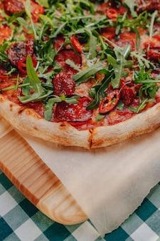 Neapolitanische pikante pizza mit schinken, käse, rucola, basilikum, tomaten, peperoni, mit käse besprüht