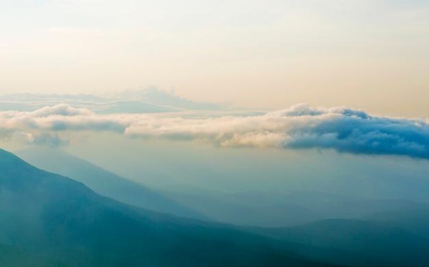 Nebel, himmel bewegen sich auf dem berg bei sonnenuntergang