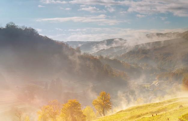 Nebelhaft ein schöner morgenherbstnebelsonnenaufgang in den bergen