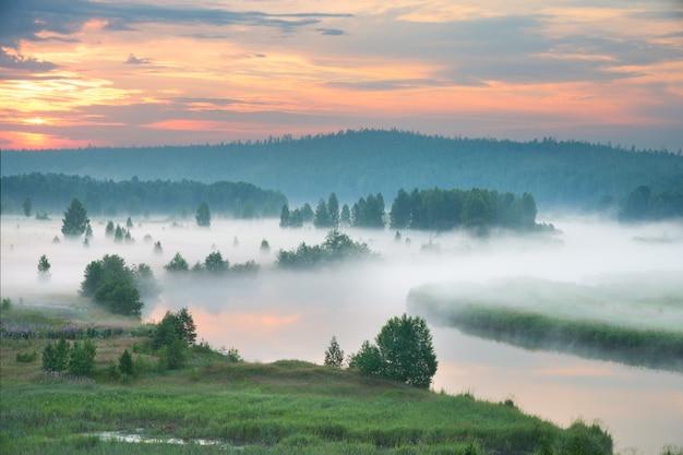 Nebelhafte morgendämmerung am fluss