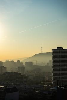Nebelhafter herbstlicher sonnenaufgang über tiflis