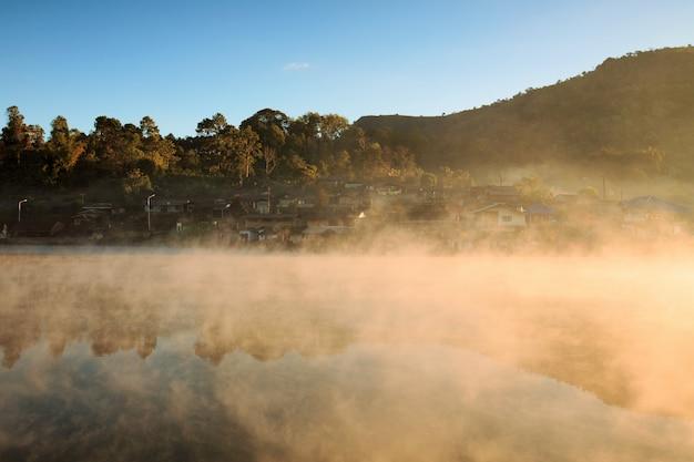 Nebelhafter morgensonnenaufgang über berg mit dorf um den fluss