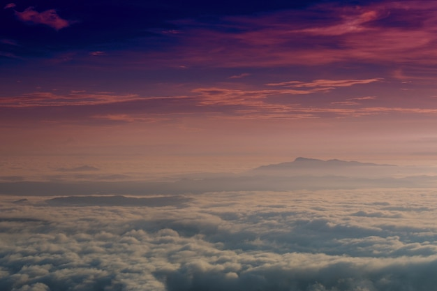 Nebeliger nebel des sonnenaufgangs bedeckte gebirgswaldlandschaft mit dunklem purpurrotem himmel