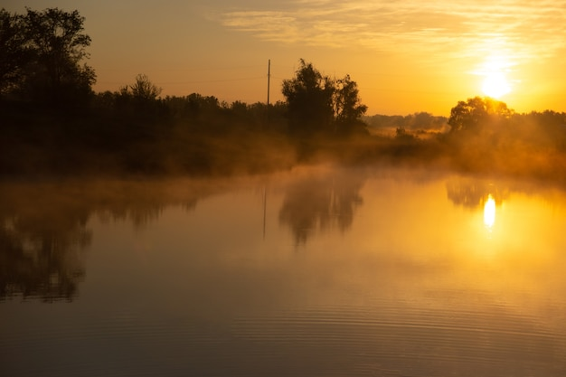 Nebeliger see am frühen morgen kurz nach goldenem sonnenaufgang.